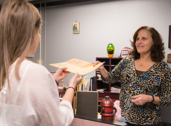 GCFD administrative staff person handing paperwork to another staff member