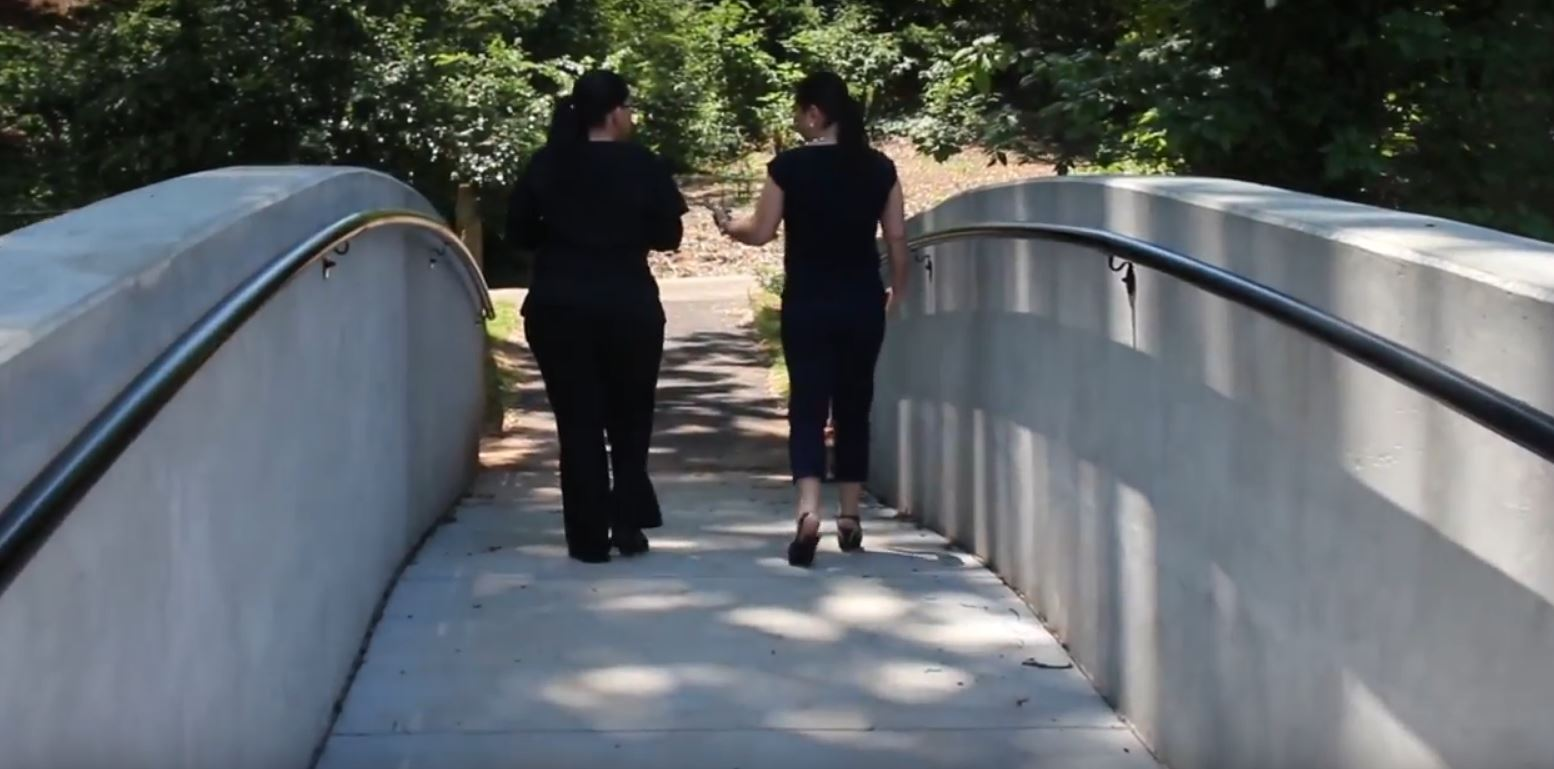 Two women walking over completed bridge in McPherson Park